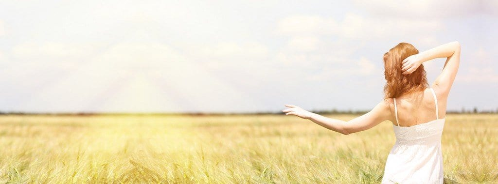 Image of selnder woman standing in field with crops suggesting participant in wellness membership program